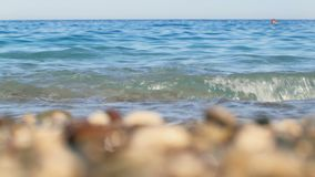 Seacoast of Turkey, focus moving from multicolor pebble to blue sea and back, in sunny day. 4K stock footage
