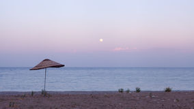 Seacoast with an umbrella from the sun at sunset in Turkey. Stock Photo
