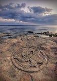 Seacoasten med forntida pictographs på vaggar arkivfoto