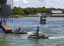 Seadoos的两个男孩在小游艇船坞附近的湖观看水的乘出租车遇到在鸭子小河的两小游艇船坞之间在盛大湖 库存图片