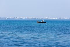 Motor boat with fishermen on background of seaside town Stock Photo