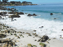 Seafoam en la playa con las rocas Fotografía de archivo