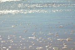 Seafoam on a sandy beach Stock Photography