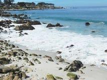 Seafoam sulla spiaggia con le rocce Fotografia Stock
