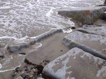 Seafoam sur les roches Images stock