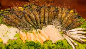 Seafood assortment: Fresh frozen mighty tiger river shrimp prawn and fish variety arrangement in front of the restaurant. Seafood. Concept stock photo