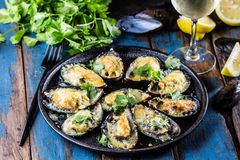 Seafood. Baked mussels with cheese and lemon in shells Royalty Free Stock Photo