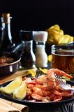 Seafood at the bar, composition of black plate with shrimp lemon beer chips royalty free stock images