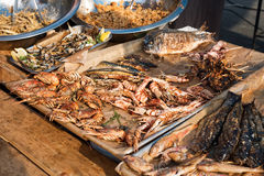 Seafood barbecue outdoors. Grilled shrimp and fish, street food mediterranean cuisine. Stock Photo