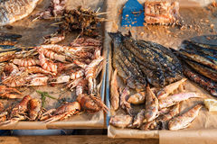 Seafood barbecue outdoors. Grilled shrimp and fish, street food mediterranean cuisine. Stock Photos