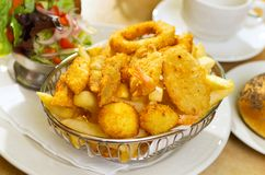 Seafood Basket. With crumbed fish,calamari,scollop,prawn with potato chips royalty free stock photo