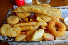 Seafood basket with battered fish fillet and crumbed prawn. Seafood basket with battered fish fillet, crumbed prawn, squid with chips stock photo