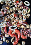 Seafood BBQ. Mixed fruits of the sea mingle on the grill for a summer feast Stock Photo