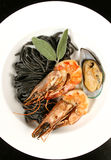 Seafood with black pasta Stock Photos