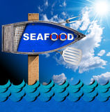 Seafood - Boat Directional Sign with Pole. Directional sign in the shape of row boat with text Seafood, kitchen utensils, blue waves and sky with clouds and sun Royalty Free Stock Photography