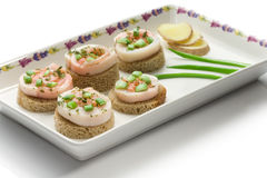 Seafood canapes on a square dish. Over white background stock images