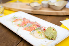 Seafood ceviche. Sea trout, scallops and shrimps with citrus-pickled onions, guacamole and cilantro   on the plate. Shallow DOF Royalty Free Stock Photos