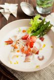 Seafood chowder with bacon and asparagus. Seafood chowder with calamari, shrimps, bacon, vegetables and asparagus on wooden table Royalty Free Stock Photos