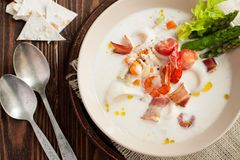 Seafood chowder with bacon and asparagus. Seafood chowder with calamari, shrimps, bacon, vegetables and asparagus on wooden table Stock Images