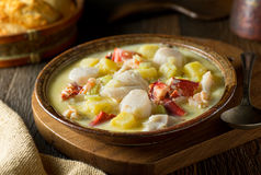 Seafood Chowder. A delicious hot bowl of homemade seafood chowder with lobster, haddock, clams, scallops, and saffron Royalty Free Stock Photography