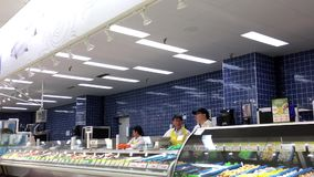 Seafood clerk stocking fish and chatting to co-worker stock video footage