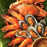 Seafood set on banana leaf. Crab, langoustine and calms cooked and served on a leaf stock image