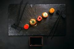Seafood delicatessen, sushi rolls set on slate royalty free stock image