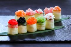 Seafood delicatessen, sushi rolls set on slate royalty free stock images