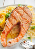 Seafood dinner of grilled salmon on linguine. Seafood dinner of a gourmet grilled salmon cutlet steak on Italian linguine pasta seasoned with fresh basil and Stock Image