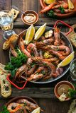 Seafood dinner. Grilled tiger prawns in grilling pan with fresh lemon, garlic, bread over wooden background, top view. Seafood dinner. Grilled tiger prawns in royalty free stock images