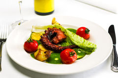 Seafood dish with fried octopus tentacles and vegetables Royalty Free Stock Photography