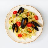 Seafood fettuccine pasta with mussels over black background. stock images