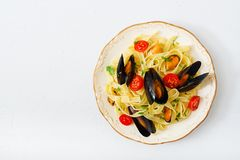 Seafood fettuccine pasta with mussels over black background. Mediterranean delicacy food. royalty free stock photos