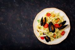 Seafood fettuccine pasta with mussels over black background royalty free stock photo