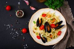 Seafood fettuccine pasta with mussels over black background. royalty free stock images