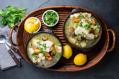 Seafood fish soup in clay bowls served with lemon and coriander. Top view, copy space Stock Images