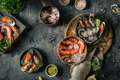 Seafood. Fresh shrimps, oysters, mussels, langoustines, octopus in ice with lemon. Thyme and other herbs in a plate on wooden boards. Luxury Food stock photo