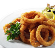Seafood - Fried Calamari. Deep-fried Squid Dressed with Salad Leaves, Parsley, Olives and Lemon. Isolated on White Background royalty free stock photography