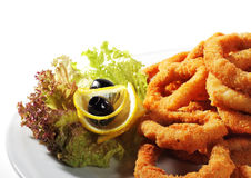 Seafood - Fried Calamari. Deep-fried Squid Dressed with Salad Leaves, Parsley, Olives and Lemon. Isolated on White Background Royalty Free Stock Photo