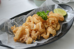 Seafood - Fried Calamari. Deep-fried Tentacles and Squid serve with parsley leaves, Olives and Lemon on black plate Royalty Free Stock Photos