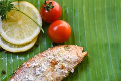 Seafood grilled fish with salt food lemon parsley tomato on banana leaf background stock images