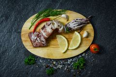 Seafood Grilled squid with herbs and spices lemon tomato chilli garlic and dill on Cutting board stock image