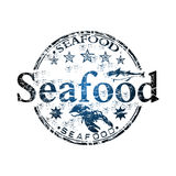 Seafood grunge rubber stamp. Blue grunge rubber stamp with small stars, fish shape, lobster and the word seafood written inside the stamp Royalty Free Stock Photo