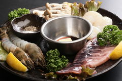 Seafood hot pot with fresh raw shrimp, squid, scallop, lemon, cu. Min, lettuce and mushroom on big black platter deliciously Stock Images
