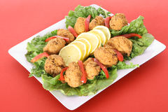 Seafood hushpuppy fritters. Isolated on red Royalty Free Stock Images