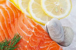 Seafood on Ice. Raw seafood on a bed of crushed ice, garnished with slices of lemon and dill, ready for cooking Stock Image