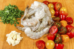 Seafood. Ingridients for spaghetti pasta with prawns or shrimps. With mixed colours cherry tomatoes fresh parsley royalty free stock photos