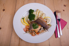 Seafood main course. On a white plate with lemon and tomato royalty free stock photos