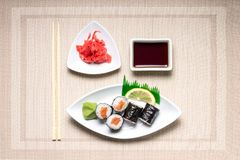 Seafood Maki-sushi rolls in white plate with chopsticks and japanese spices Stock Image
