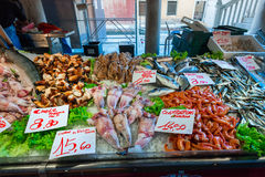 Seafood market with price list. Fresh fish, shrimp, crab and squid on ice stock image